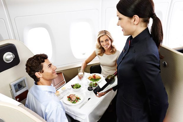 A flight attendant serving two First Class passengers