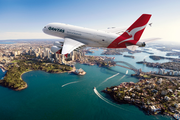 Qantas plane flying over Sydney with the bridge and opera house in the background