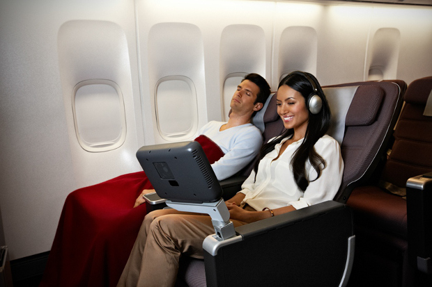 A passenger in premium economy watching their entertainment screen