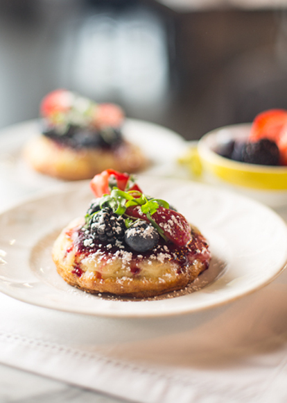 A crumpet on a plate topped with berries and syrup