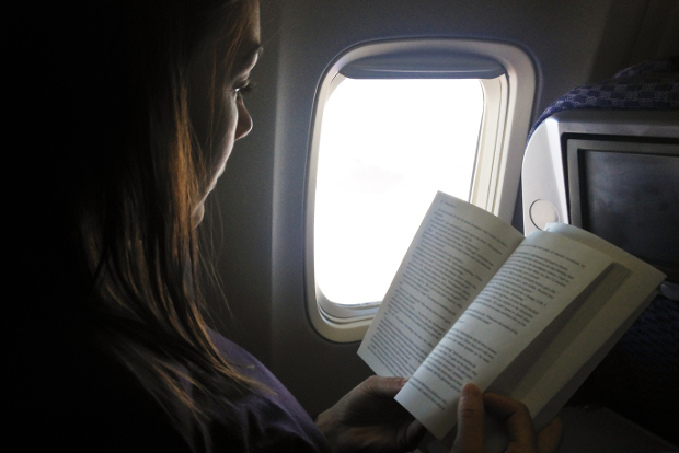A girl reading a book on an airplane