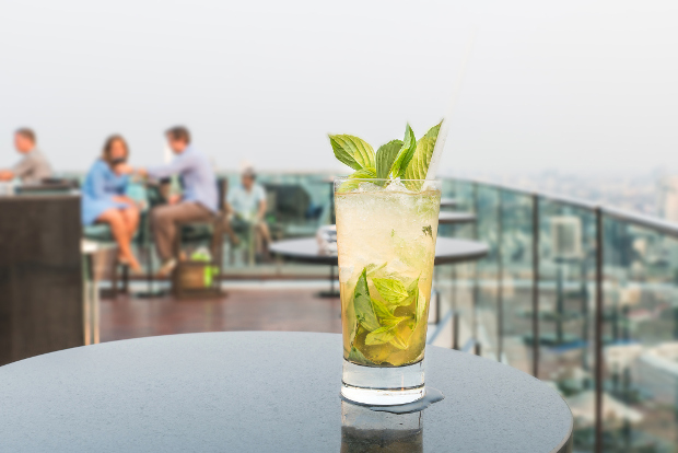 A cocktail sitting on a table at a rooftop bar