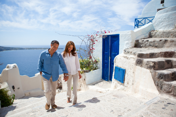 A couple walking along a stone path in Santorini