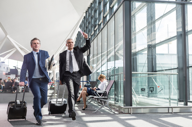 Two business men rushing through the airport with their carry-ons to catch their flight