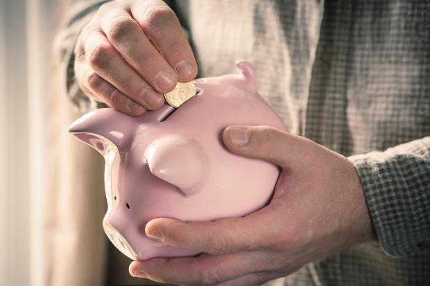 A man putting a gold coin in a piggy bank