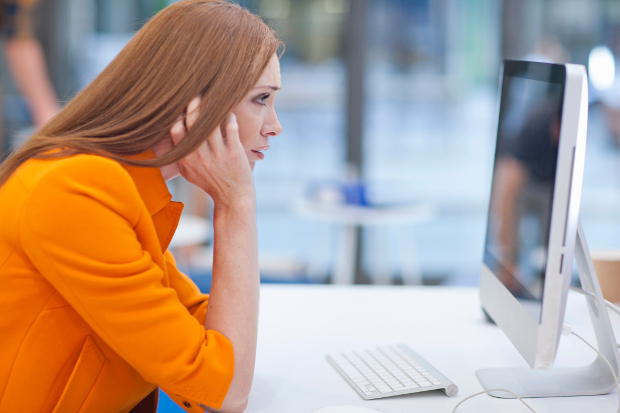 An exasperated woman looking at a computer screen