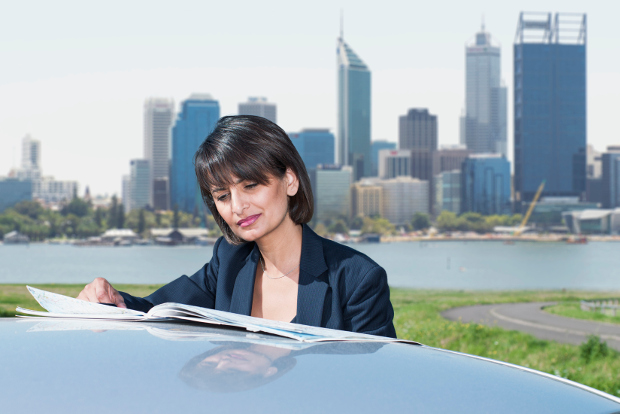 A woman reads a map on the roof of her car, with a city skyline behind her.