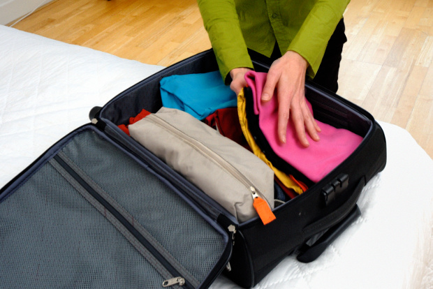 A woman packs her suitcase.