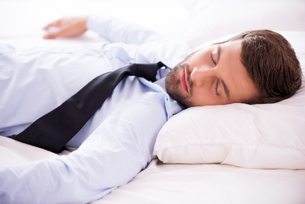 Business man sleeping on a bed