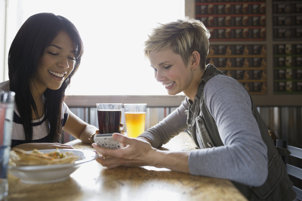 Two friends laughing at a restaurant