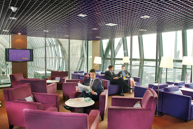 A view of the seating area available at one of Thai Airways' lounges with seated travellers relaxing before their flight