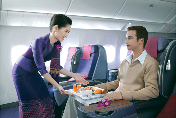 A passenger being served his meal in Thai Airways Business Class