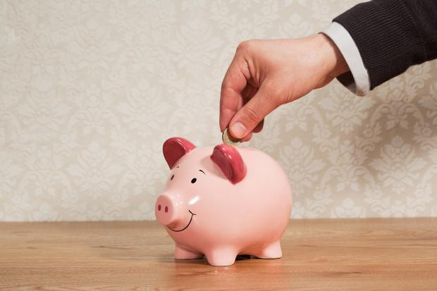A man putting a coin in a piggy bank