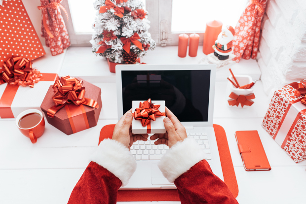 A person dressed as santa holding a gift in front of a laptop computer on a desk