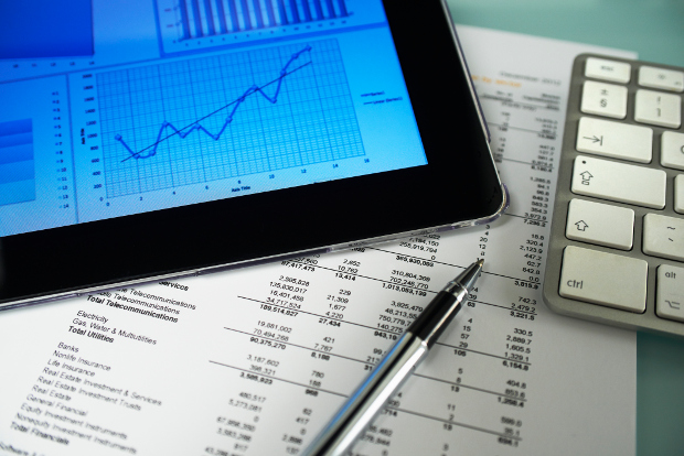 A tablet with a graph with budget paperwork