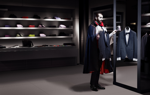 A man dressed as a vampire shopping for new clothes