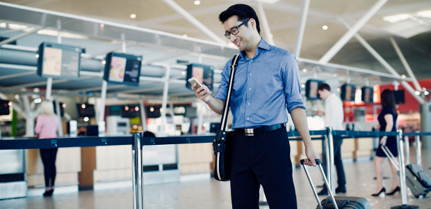 A man happily looking at his mobile phone as he walks through the airport