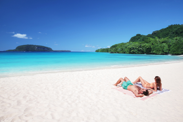 A couple relax on Champagne Beach in Vanuatu.