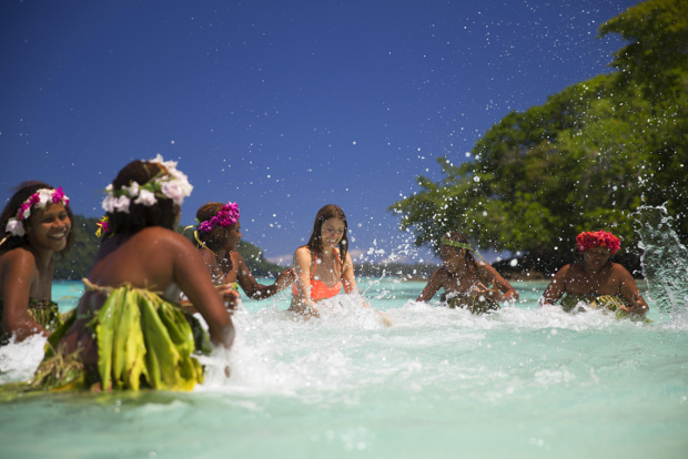 Ni-Vanuatu women splash in the water with a tourist.