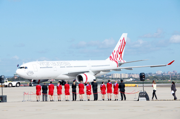 Virgin flight crew standing on the runway looking at a Virgin plane