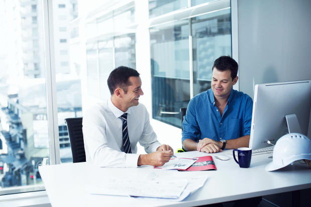 Two professional men talk business travel at an office desk
