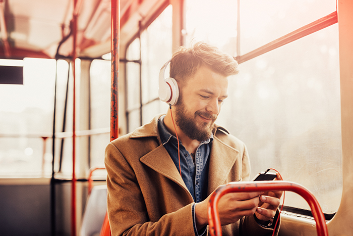 Man listening to business podcast while travelling