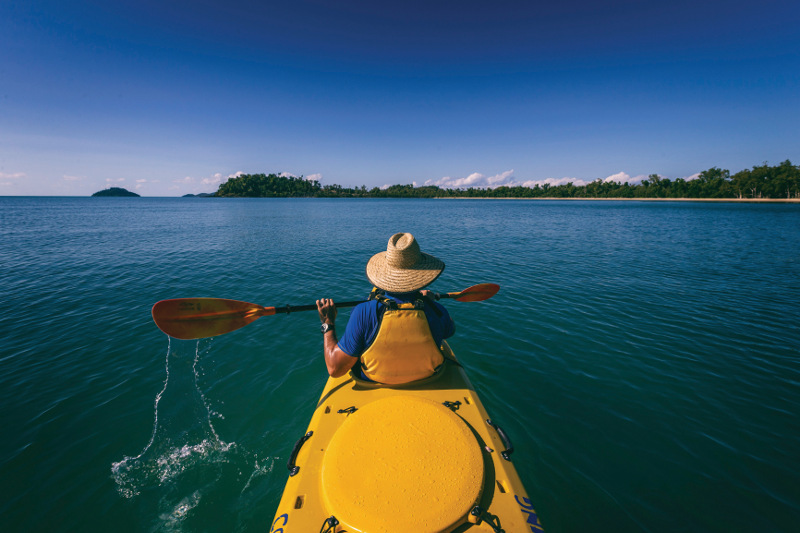 Man in a sea kayak paddles on water near Cairns