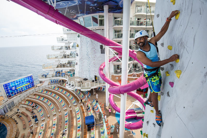 man on rock climbing wall above ship in ocean