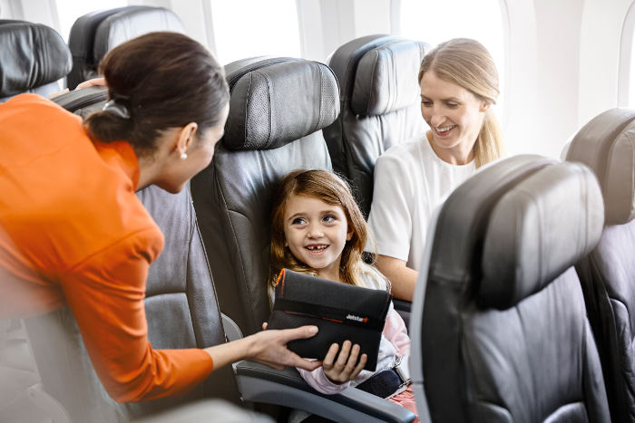 jetstar cabin crew giving young girl amenity kit