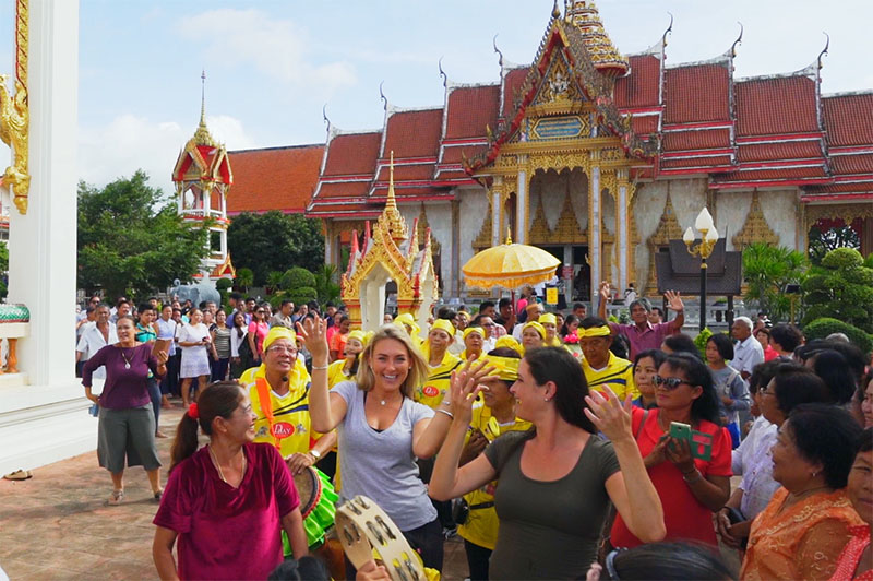 greer and rhi dancing with locals at wat chalong temple