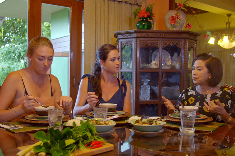 greer and rhiannon sitting down with pat to eat the food they've cooked