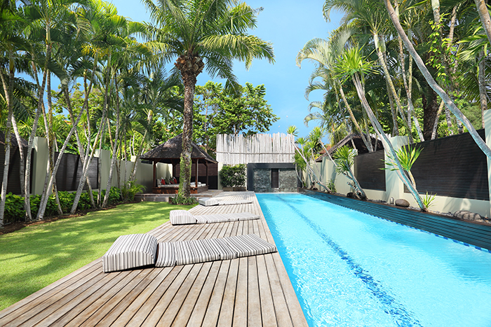 Wooden pool deck with sofa beds and pool at the hotel