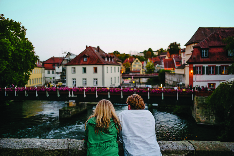 couple on bridge in european town