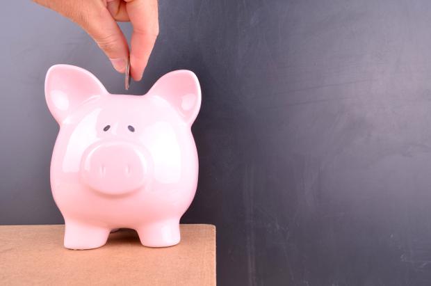 A person putting a coin in a piggy bank
