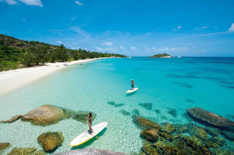 couple stand up paddle boarding over clear waters on lizard island beach qld