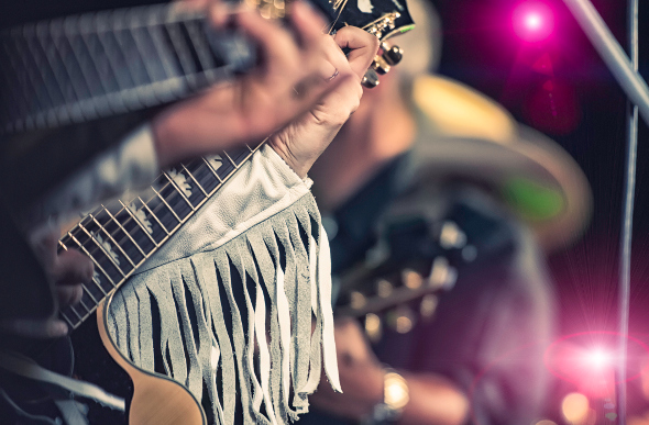 A close-up of a country music guitarist.