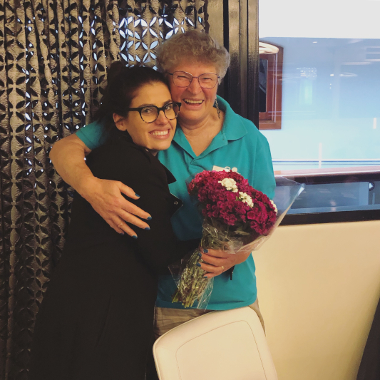 Sheridan and Aida hugging and smiling towards the camera. Aida holding a punch of flowers