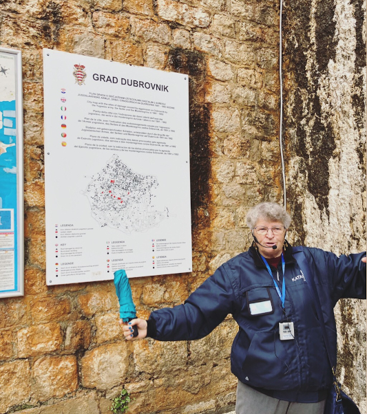 Aida standing in front of a map that shows the damage to the Old Town of Dubrovnik during the war