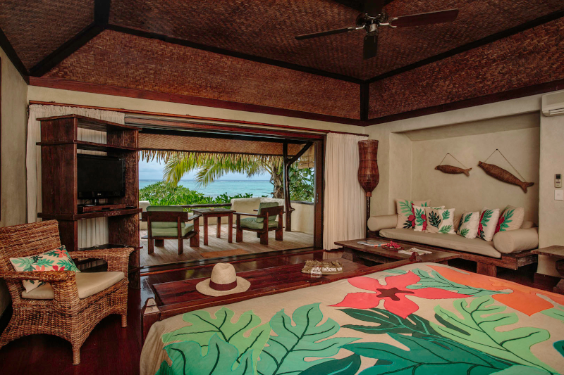 Interior of hotel room looking out to the ocean and tropical garden. There are a lot of wooden features in the room