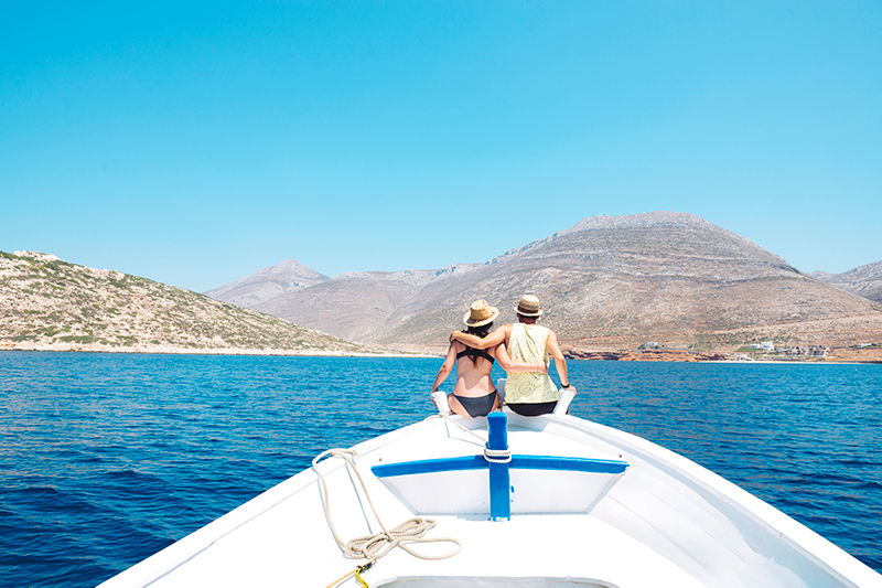 A couple on a boat looking at Amorgos island