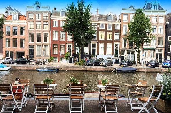 Cafe chairs beside amsterdam canal