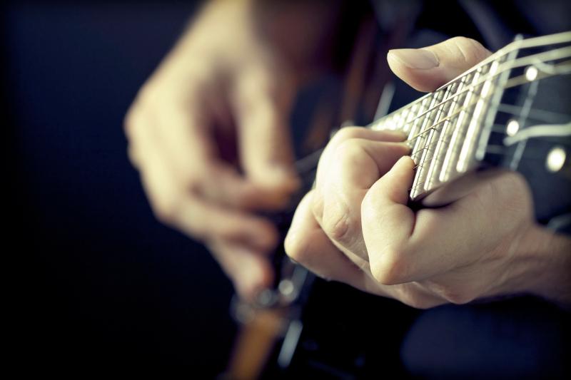 A close-up of a man playing guitar.