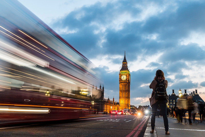A woman takes a photo of Big Ben as a bus whizzes by in London's twilight.