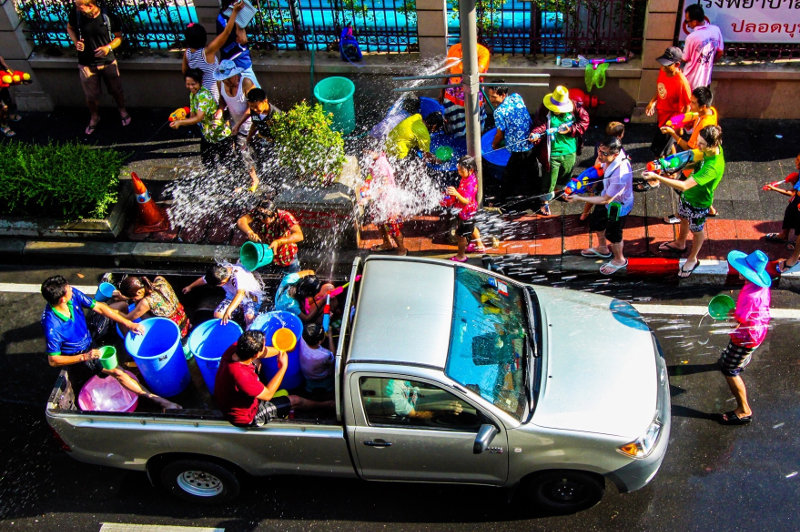 People in a ute throw buckets of water on a crowd during Songkran in Thailand.