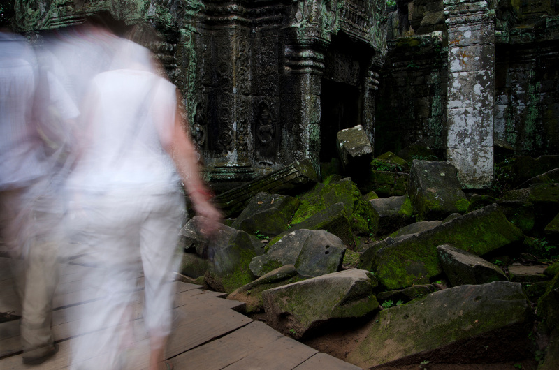 Blurred images of people walking through a ruined temple deep in shadow in Angkor, Cambodia.
