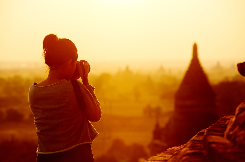 A young woman photographs the temples of Bagan in Myanmar at sunset.