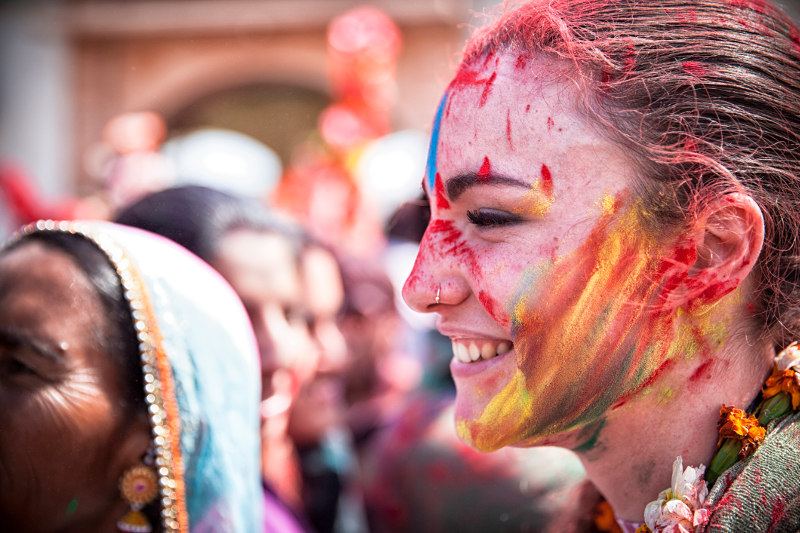 A young woman is covered in coloured powder during the Holi festival in India.
