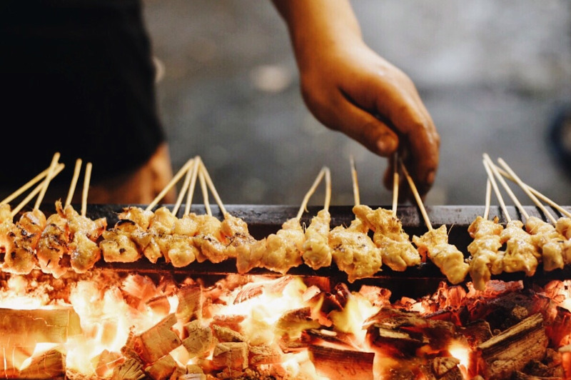 A close-up of a hand cooking satays over a fire in Kuala Lumpur, Malaysia.