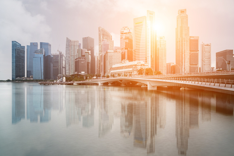 The Singapore skyline against a peachy-golden sky.