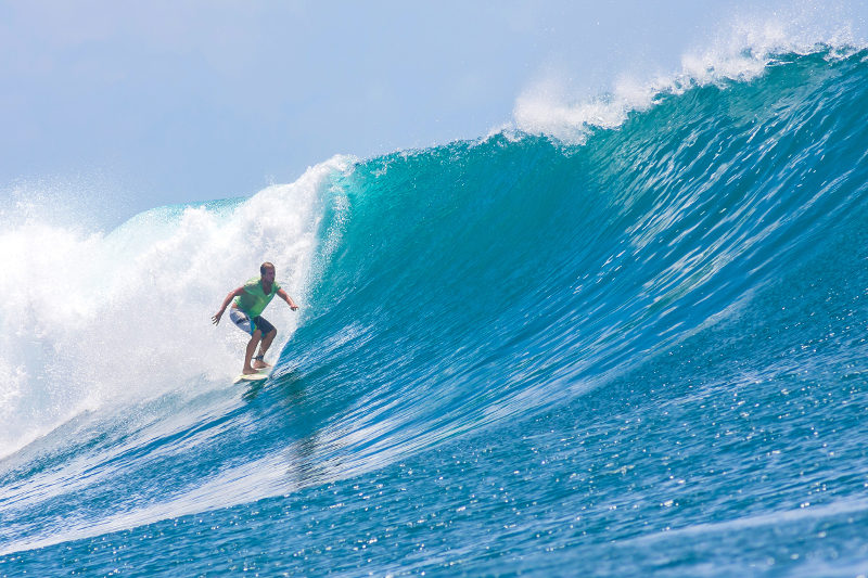 A surfer rides a wave in Lombok, Indonesia.